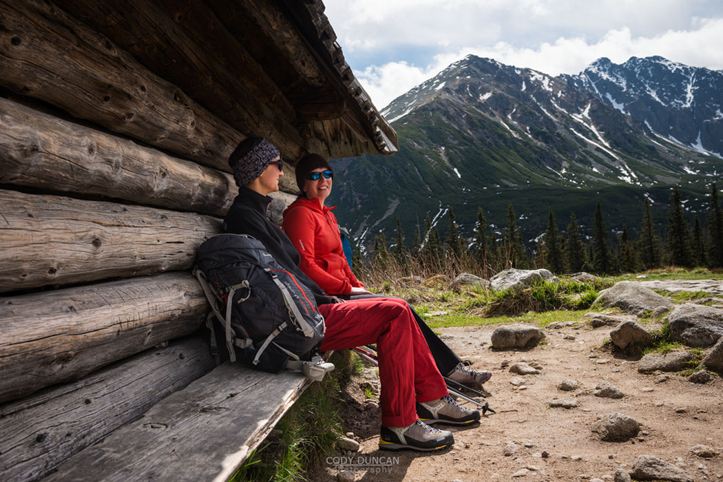 Two female hikers sit outside mountain barn, Tatra mountains, Poland