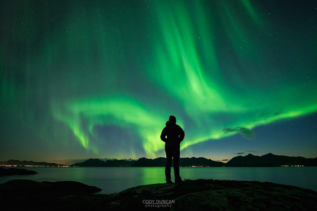 Silhouette of person watching Northern Lights - Aurora Borealis  over coastline, Austvågøy, Lofoten Islands, Norway