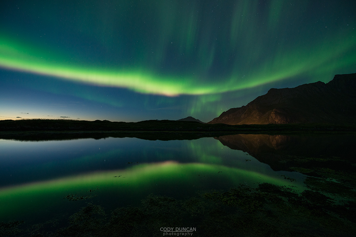 Reflection of northern lights in sky over mountains of Flakstadøy, Lofoten Islands, Norway